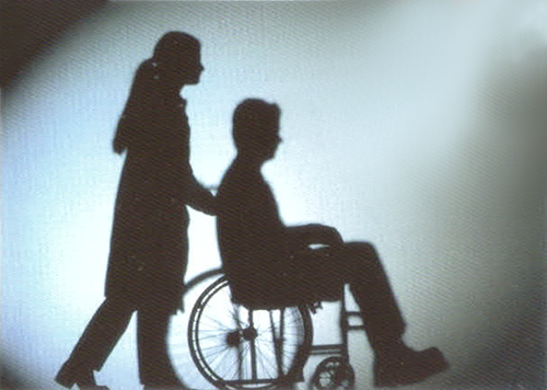 Silhouette of wheelchair user and carer